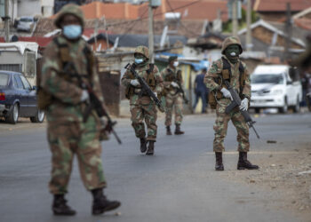 South African National Defence Forces patrol the streets at a densely populated Alexandra township east of Johannesburg, South Africa, Saturday, March 28, 2020. South Africa went into a nationwide lockdown for 21 days in an effort to mitigate the spread to the coronavirus. The new coronavirus causes mild or moderate symptoms for most people, but for some, especially older adults and people with existing health problems, it can cause more severe illness or death. (AP Photo/Themba Hadebe)