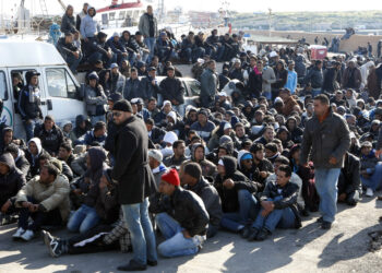 Illegal immigrants from North Africa arrive on the southern Italian island of Lampedusa February 13, 2011. More than 1,000 people escaping turmoil in Tunisia have landed on Lampedusa, a Sicilian island closer to Africa than mainland Italy, in rickety boats this week, raising fears of a new, uncontrolled wave of illegal immigration from North Africa. In two days 1,114 migrants arrived, including 113 on a large boat and nine Tunisians who were rescued from a small dinghy before it sank.REUTERS/Antonio Parinello (ITALY - Tags: POLITICS SOCIETY IMAGES OF THE DAY)