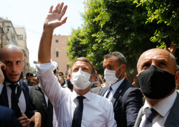 French President Emmanuel Macron gestures towards residents as he visits a devastated street of Beirut, Lebanon, on August 6, 2020 a day after a massive explosion devastated the Lebanese capital in a disaster that has sparked grief and fury. - French President Emmanuel Macron visited shell-shocked Beirut Thursday, pledging support and urging change after a massive explosion devastated the Lebanese capital in a disaster that has sparked grief and fury. (Photo by Thibault Camus / POOL / AFP)