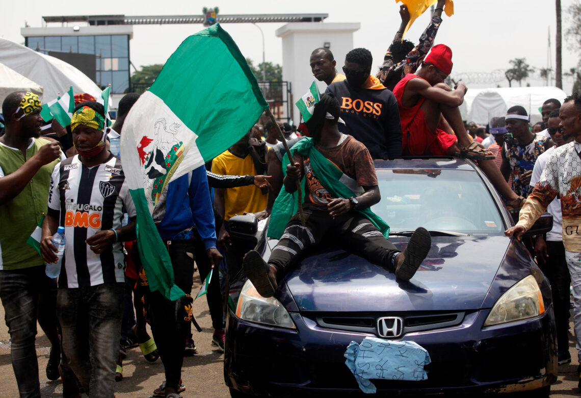 epa08758036 Protesters sit atop a vehicle with the Nigerian flag as they shout slogan near the Lagos governor's office during a protest against the Nigeria rogue police, otherwise know as Special Anti-Robbery Squad (SARS), in Ikeja district of Lagos, Nigeria, 19 October 2020. It has been two weeks since a protest against SARS began and Protesters say agitation against police brutality continues as an entry point to addressing other social and political issues such as corruption, official ineptitude to public accountability, and government inefficiency in Nigeria.  EPA-EFE/AKINTUNDE AKINLEYE