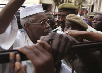 FILE In this Nov. 25, 2005 file photo, former Chad dictator Hissene Habre, left, is seen as he leaves the court in Dakar, Senegal. For more than 20 years, former Chadian dictator Hissene Habre lived a life of luxurious exile in Senegal, taking a second wife and watching 'Seinfeld' shows. But 3,000 miles east of here, a truth commission and rights workers in Chad were documenting widespread abuses during Habre's rule, including disappearances, torture and prison cells so cramped that inmates often died for lack of air. On Tuesday, July 2, 2013, judges at a special court in Dakar formally charged Habre with crimes against humanity, war crimes and torture. (AP Photo/Schalk van Zuydam, File)